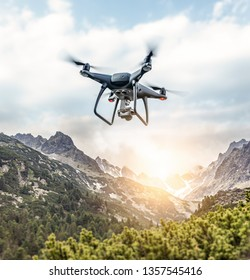 Modern drone flies in the mountains. Dark drone in the air against the backdrop of a mountain landscape.