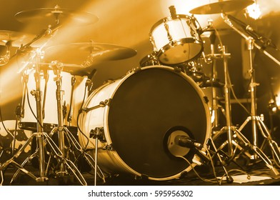 Modern drum set on stage prepared for playing in bright blue light