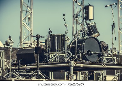 Modern drum set on stage prepared for playing in bright blue light. music installation with drums standing outdoors stage before concert. Drum kit on stage in the spotlight color