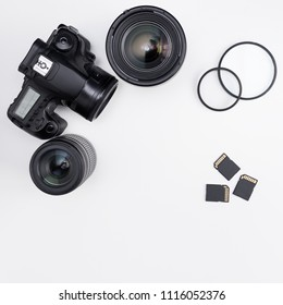 modern dslr camera, lenses, photo equipment and copy space over white table background