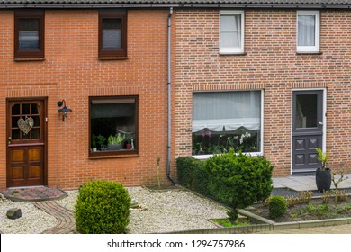 Modern dutch terraced house exterior with gardens, plants behind the windows, homes in a dutch village