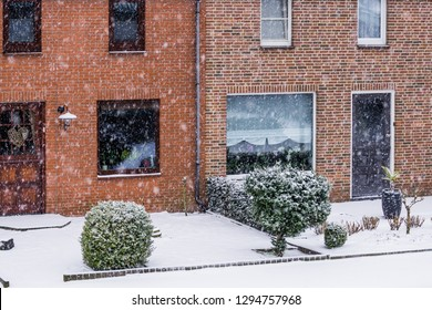 modern dutch terraced houses with a garden during a cold winter day, snowy weather in a small village of the Netherlands