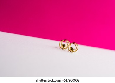 Modern earrings on a white and pink background shot wide