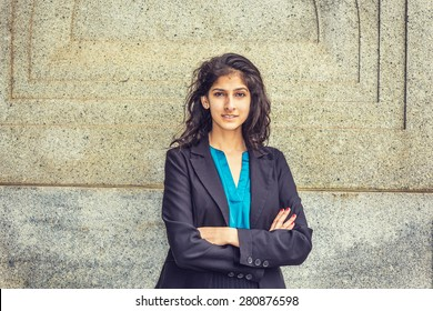 Modern East Indian American Student. Dressing in black blazer, blue under shirt, crossing arms,  a young girl with long curly hair standing by wall, smiling, looking at you. Instagram filtered effect.