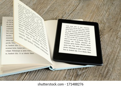 modern ebook reader on book on wooden table