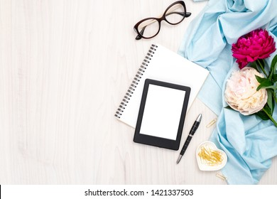 Modern ebook reader, paper notepad, peonies flowers, glasses, golden stationery on wooden background. Top view, minimal flat lay style composition. Women desk, fashion blogger, beauty technology