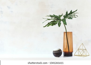 Modern and eclectic room interior with abstract wiped walls, gold pyramid and tropical leaf in vase .Stylish space with design accessories. Eclectic home decor. Real photo. Copy space for inscription.