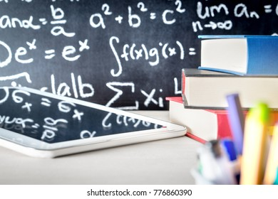 Modern education and e learning tools in school classroom table. Stack of books, tablet and pens with blackboard full or writing. Digital teaching and studying online concept.