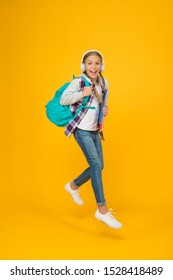 Modern education. Energetic cheerful teen listening music. Stylish schoolgirl going to school. Girl little fashionable girl carry backpack. School daily life. Happy carefree child. School and leisure.