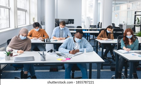 Modern Education And Studying During Pandemic Concept. Diverse group of international students sitting at desks in classroom at high school, wearing protective medical mask, writing in notebooks