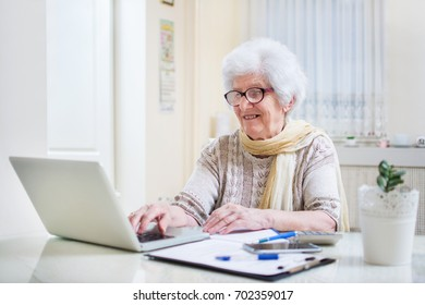 Modern elderly woman using laptop and calculating bills at home.