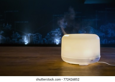 Modern electric aroma diffuser machine in operation on wooden table