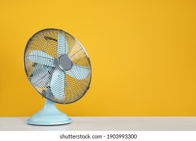 Modern electric fan on white table. Space for text
