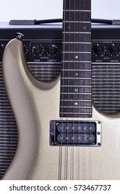 Modern electric guitar propped up against a guitar amplifier.