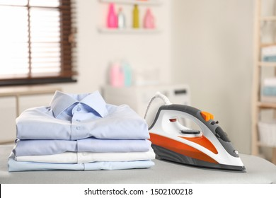 Modern electric iron and folded clothes on board in laundry room. Space for text