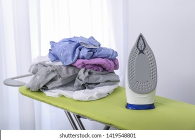 Modern electric iron and heap of clothes on board indoors. Laundry day