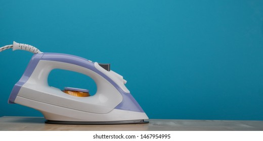 Modern electric iron on blue background