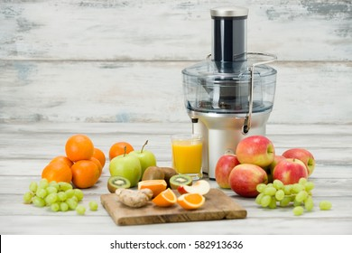Modern electric juicer, various fruit and glass of freshly made juice, healthy lifestyle concept. New year's resolution, fresh start, losing weight concept.