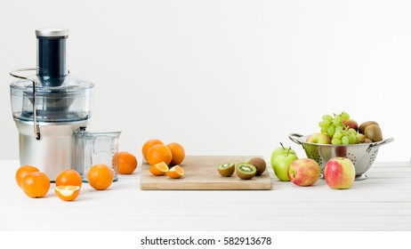 Modern electric juicer and various fruit on kitchen counter, healthy lifestyle concept. New year's resolution, fresh start, losing weight concept.