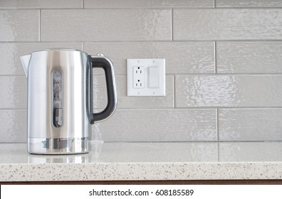 Modern electric stainless steel kettle on a granite counter top against a ceramic background