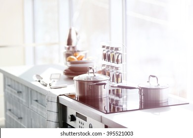 Modern electric stove with utensils in the kitchen beside window