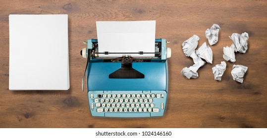 Modern electric typewriter on wooden desk background with papers ready for a new book or novel with many failed pages screwed up on desktop