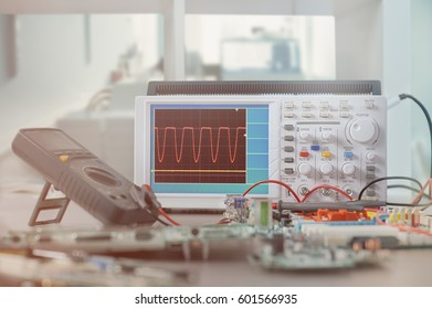 Modern electronic equipment in computer service center, including oscilloscope and solder. This image is toned