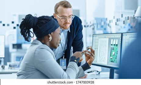 Modern Electronics Factory: Female Supervisor Talks to a Male Electrical Engineer who Works on Computer with CAD Software. Designing PCB, Microchips, Semiconductors and Telecommunications Equipment