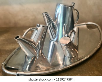 Modern elegant metal tea set on a tray.
