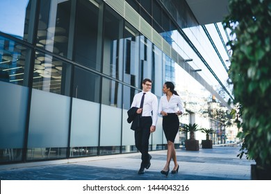 Moderne, elegante, multiethnische Frau und Mann, die die Straße entlang spazieren gehen und sich nach der Arbeit am Glasbau fröhlich entspannen