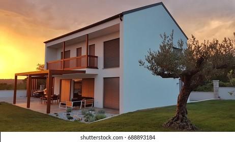 Modern elegant prefabricated house at sunset