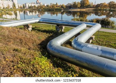 Modern Elevated Heat Pipes. Pipeline above ground, conducting heat to heat city. Urban line in metal insulation in residential quarter of city. Open laying on pillars. Municipal Pipes supply