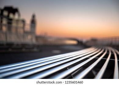 Modern empty iron bench with curved shapes along a boulevard or in a park. Blurred background with aluminum colors and lighthouse on the back