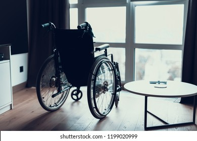 Modern Empty Wheelchair stand near Window in Room. Silhouette of Black Invalid Chair for Disabled People Parked in Bright Patients Living Room near Large Panoramic Window.