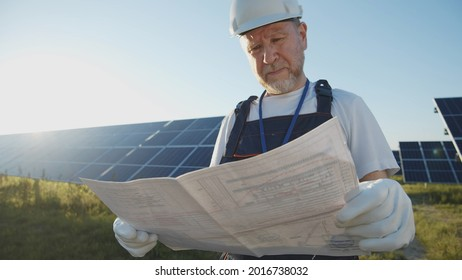 Modern engineer of solar power plant checking work standing across the batteries on green sunny summer field. Futuristic technology innovation. Ecology and environment. Eco-friendly system.