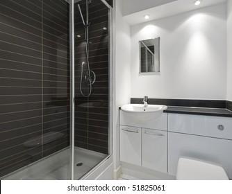 modern en-suite bathroom with a shower cabin and dark ceramic tiles