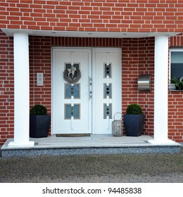Modern entry door with a front garden of the house -