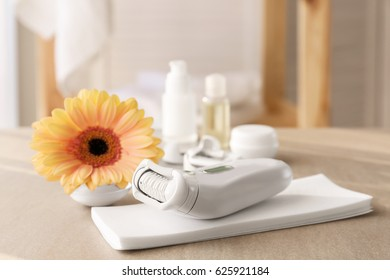 Modern epilator and wax strips on table at home