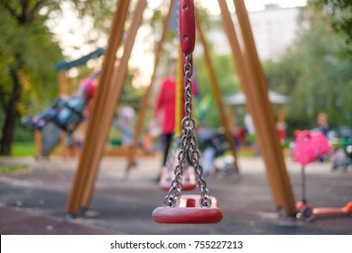 Modern equipped kids playground in sunny day. Kids and parents on chain swings