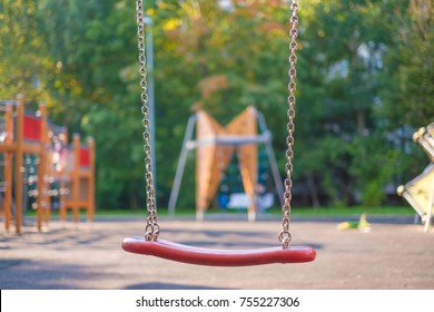 Modern equipped kids playground in sunny day. Chain swings