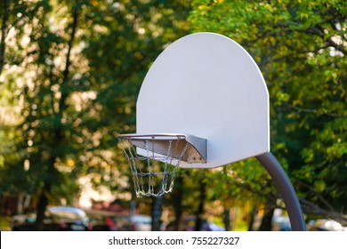 Modern equipped kids playground in sunny day. Basketball backboard on blurry background