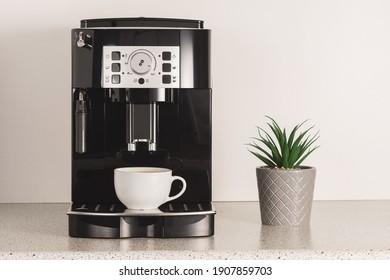 Modern espresso coffee machine with a cup in kitchen.