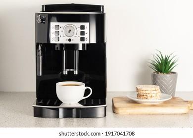 Modern espresso coffee machine with a cup in interior of kitchen closeup.