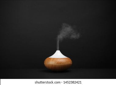 Modern essential oil diffuser on black background. Space for text