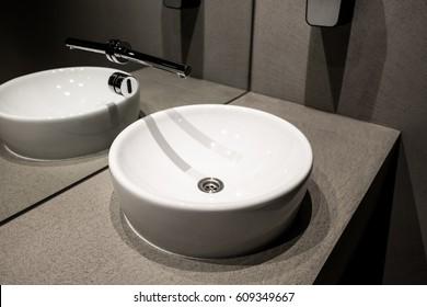 Modern european ceramic sink, Washstands with photocells, Luxury public toilet with wash basins, Public toilet with modern sink in detail, Design basin in dark bathroom