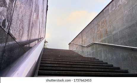 The modern exit from the pedestrian tunnel is empty, up the stairs. Staircase up to the street from the underpass. Stainless steel.