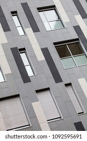Modern external facade of a building. Shades of gray and white. With vertical rectangles. Horizontal and vertical windows. Outer surface.