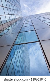 modern facade of glass and steel with reflections of the blue sky