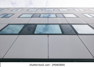 modern facade of university office buildings and reflections of clouds in windows