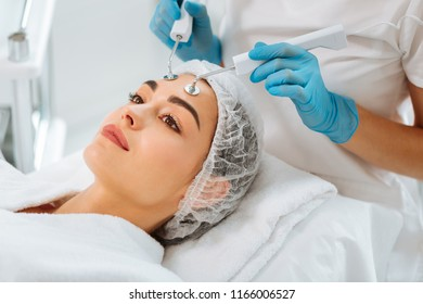 Modern facial treatment. Nice positive woman lying on the medical bed while having microcurrent therapy procedure
